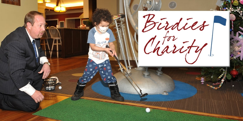 Chris Gumbach, PGA Professional (River Forest CC), helps a patient at Ronald McDonald House with his putting stroke